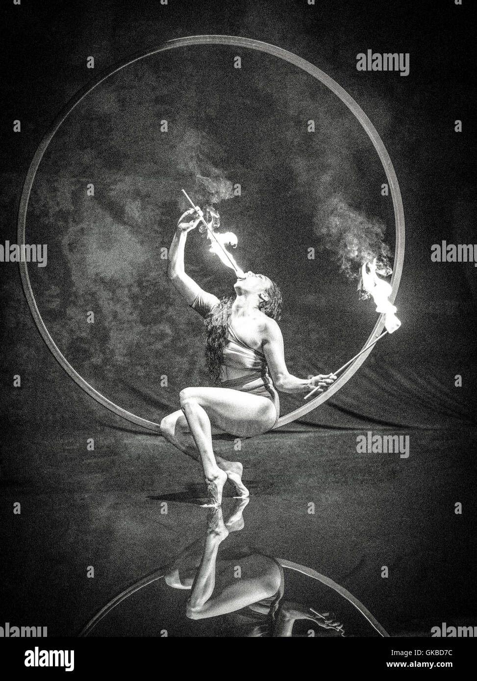Fire-eating woman sitting on a floating ring above a reflection pool - Stock Image
