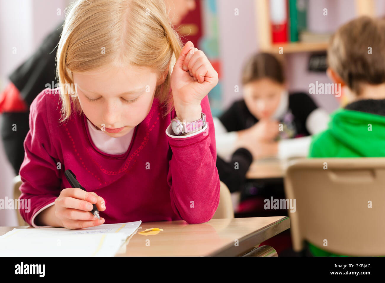 schoolchildren and teacher learning at school - Stock Image