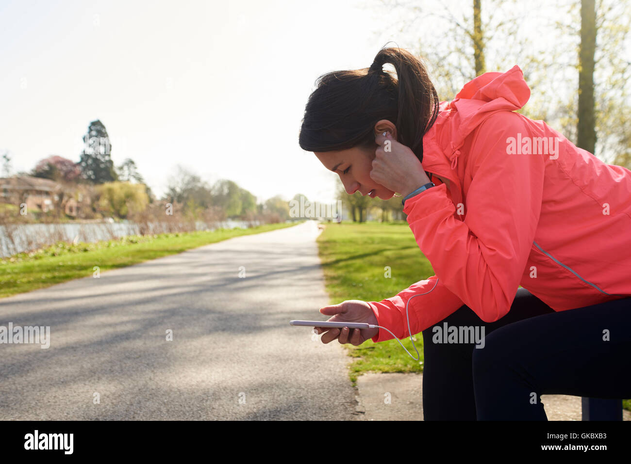 Woman Resting On Park Bench With Cellphone During Exercise - Stock Image