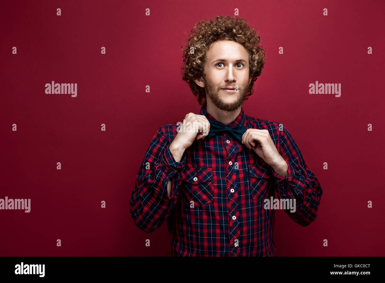 Portrait of surprised curly-haired man in checked shirt and bow-tie on red background. Isolate - Stock Image