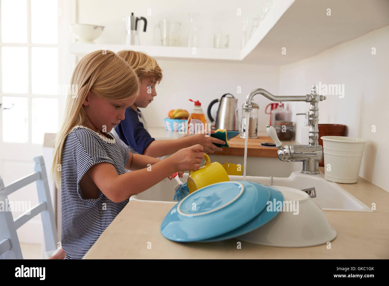 Brother and sister kneeling on chairs to wash up in kitchen - Stock Image