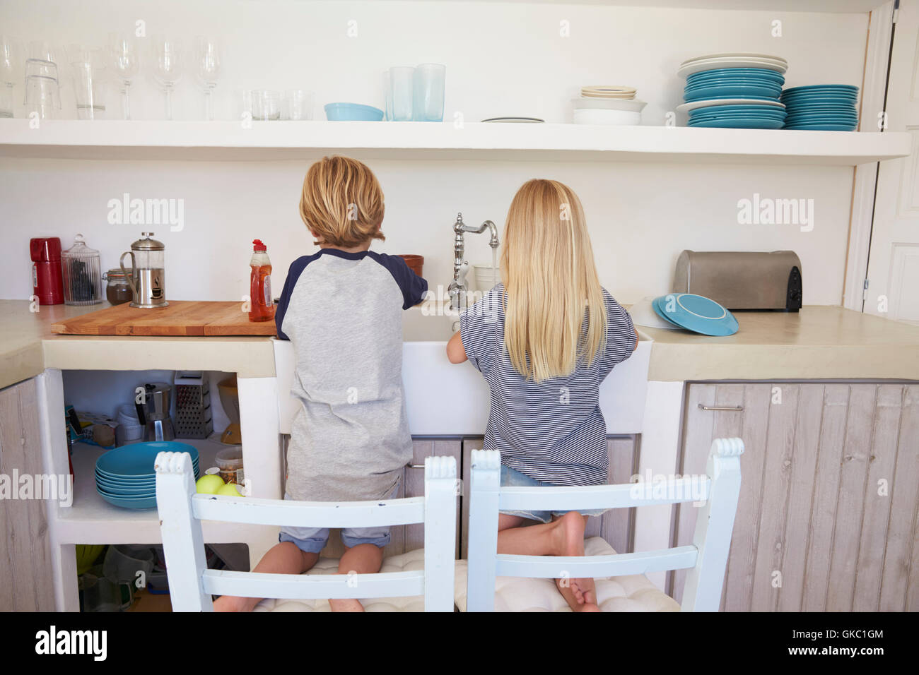 Brother and sister kneeling on chairs to wash up, back view - Stock Image