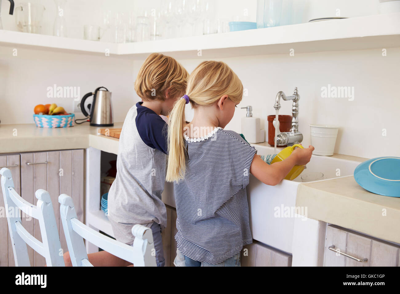 Brother and sister kneeling at sink to wash up in kitchen - Stock Image