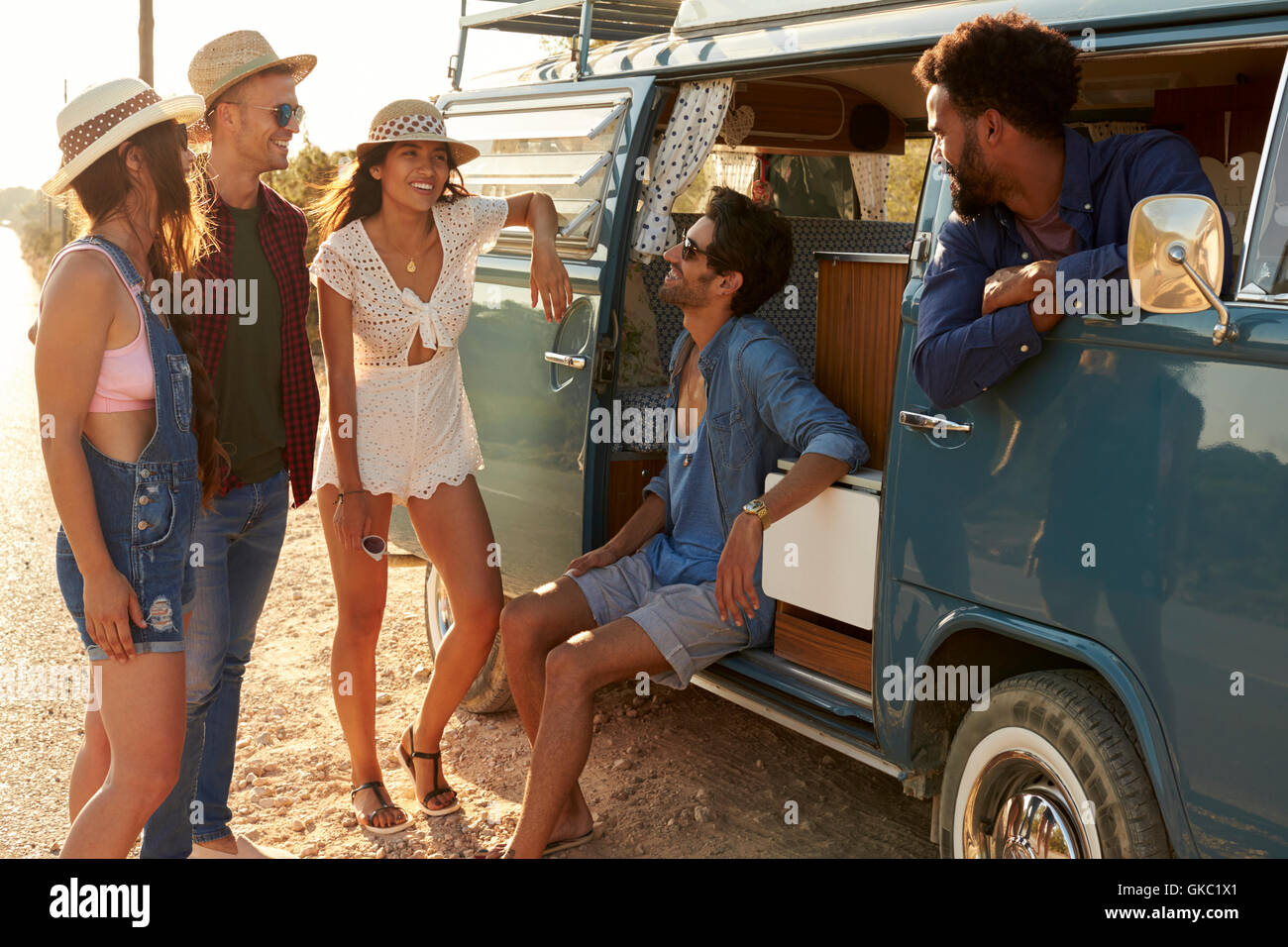 Friends on a road trip hanging out by their camper van - Stock Image