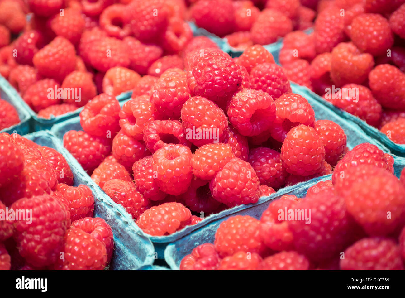 Punnets of fresh raspberries for sale at Granville Island Public Market in Vancouver, British Columbia, Canada. - Stock Image