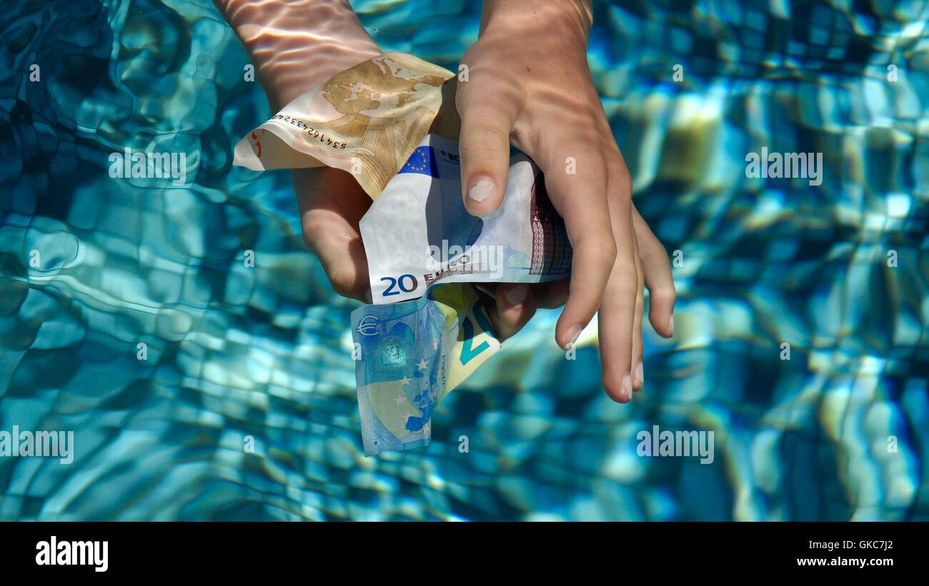 Hands grabbing euros under water. - Stock Image