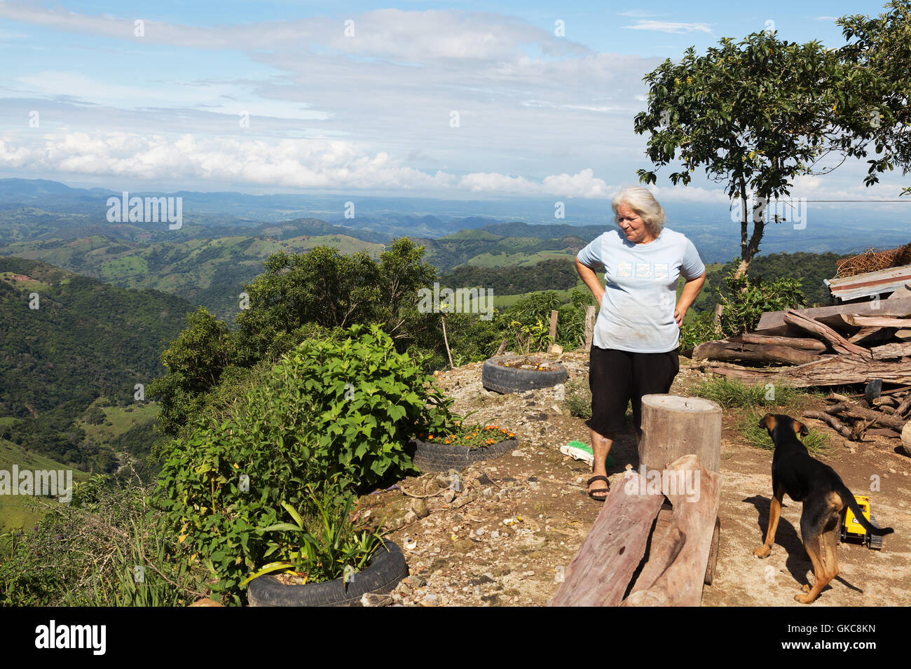 A local costa rican woman and her dog looking out over the countryside, the central highlands near Monteverde, Costa - Stock Image