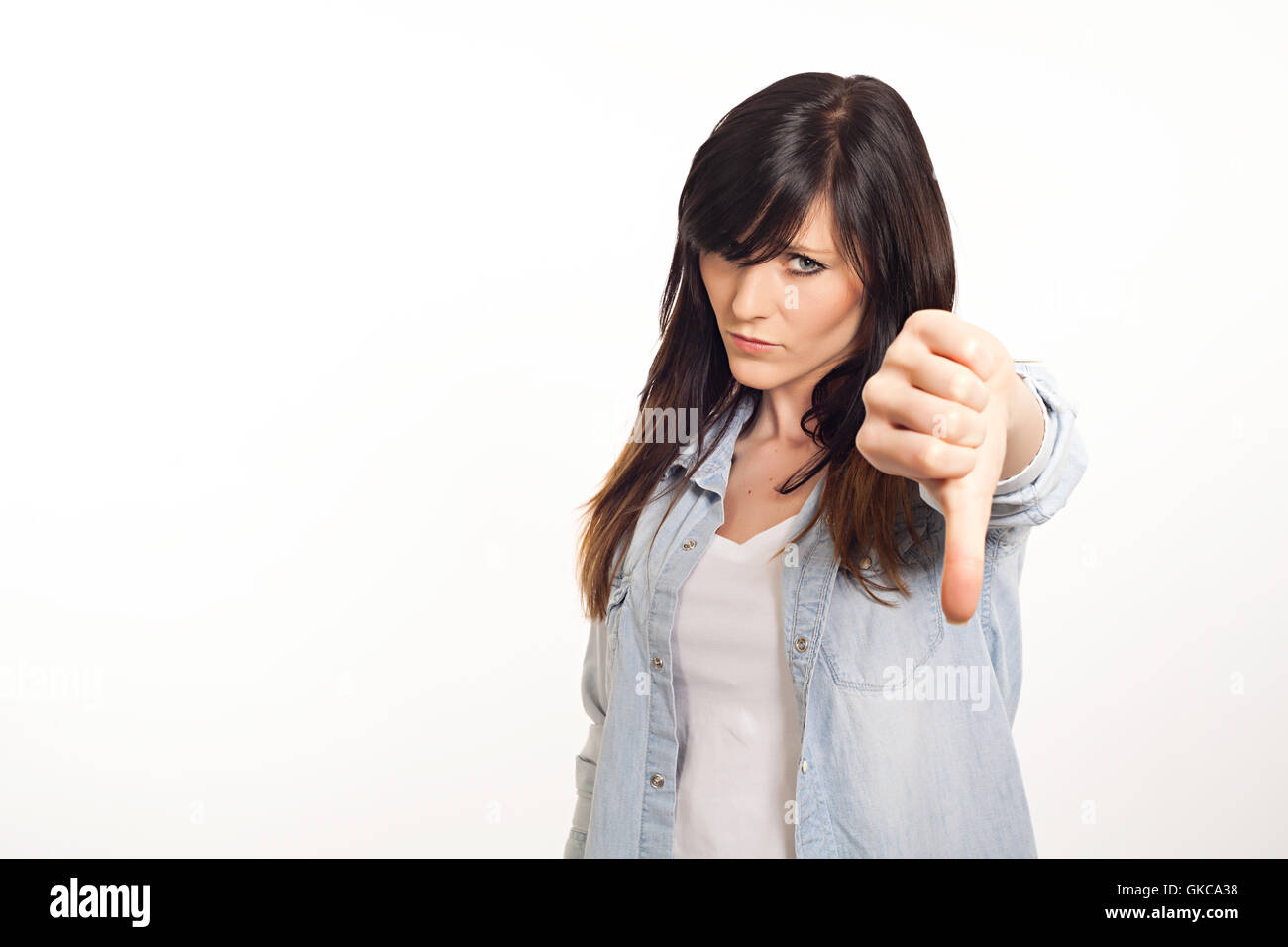 portrait of a beautiful young woman thumbs down - Stock Image