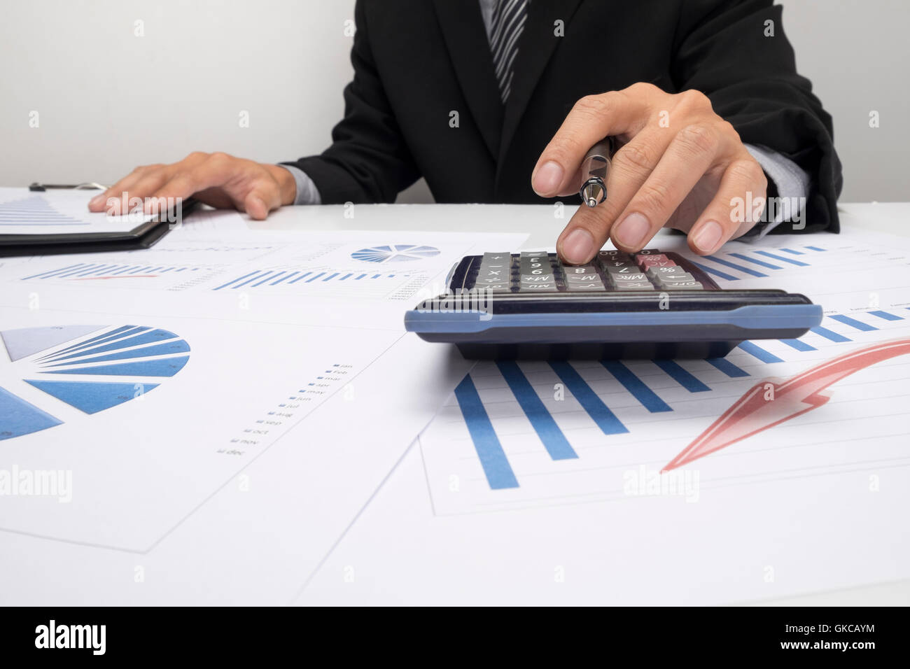 Asian Business man using a calculator to calculate the numbers - Stock Image