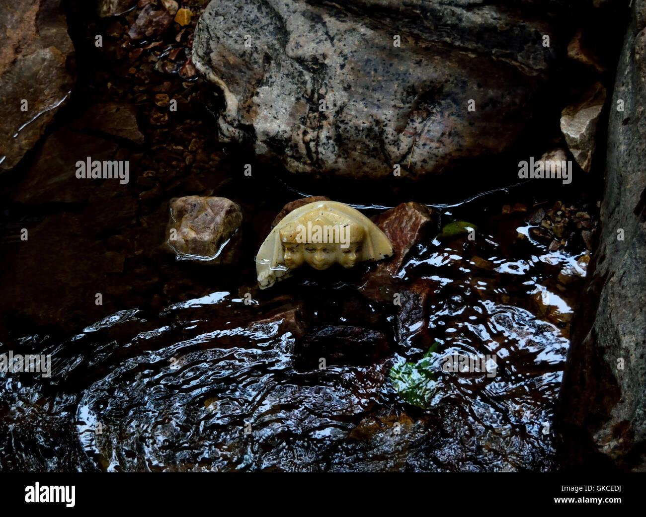 A desecrated Hindu marble idol with three heads lying in the Garvaji waterfall in Alwar Rajasthan India - Stock Image