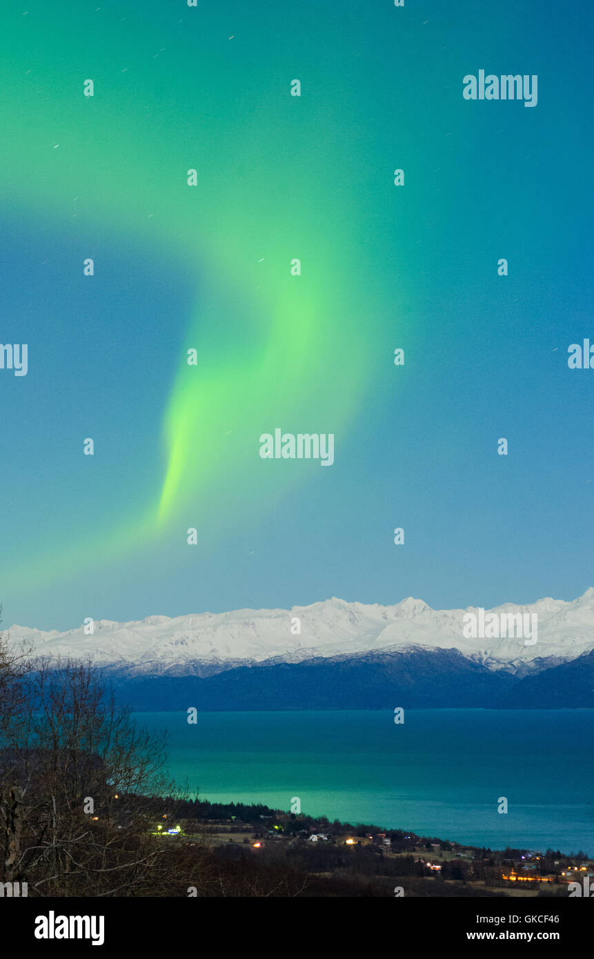 As an aurora spreads out, the light causes Kachemak Bay to glow green. - Stock Image