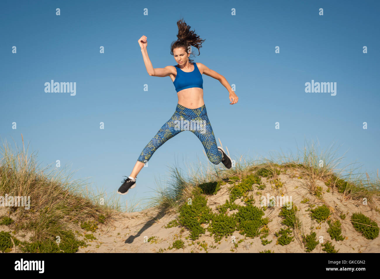 woman exercising, running and jumping in sand dunes - Stock Image