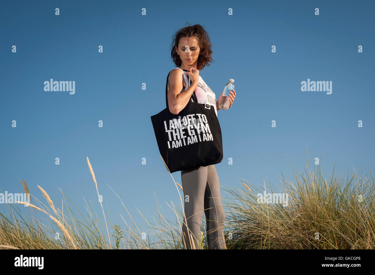 woman with water bottle and bag, I'm off to the gym I am I am - Stock Image