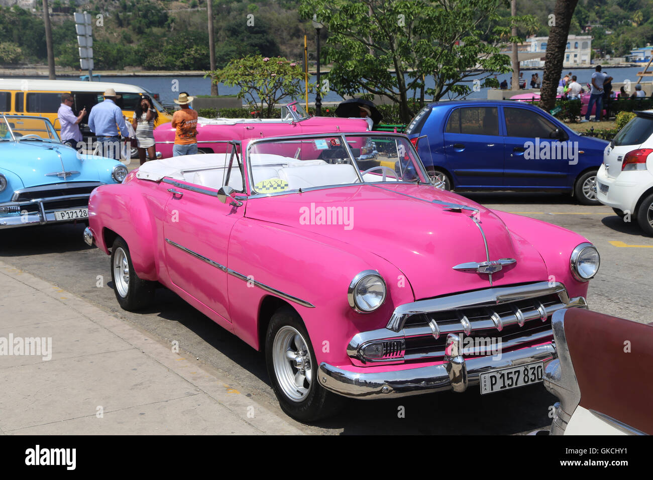 A classic old America car, painted pink, is parked in Havana\'s old ...