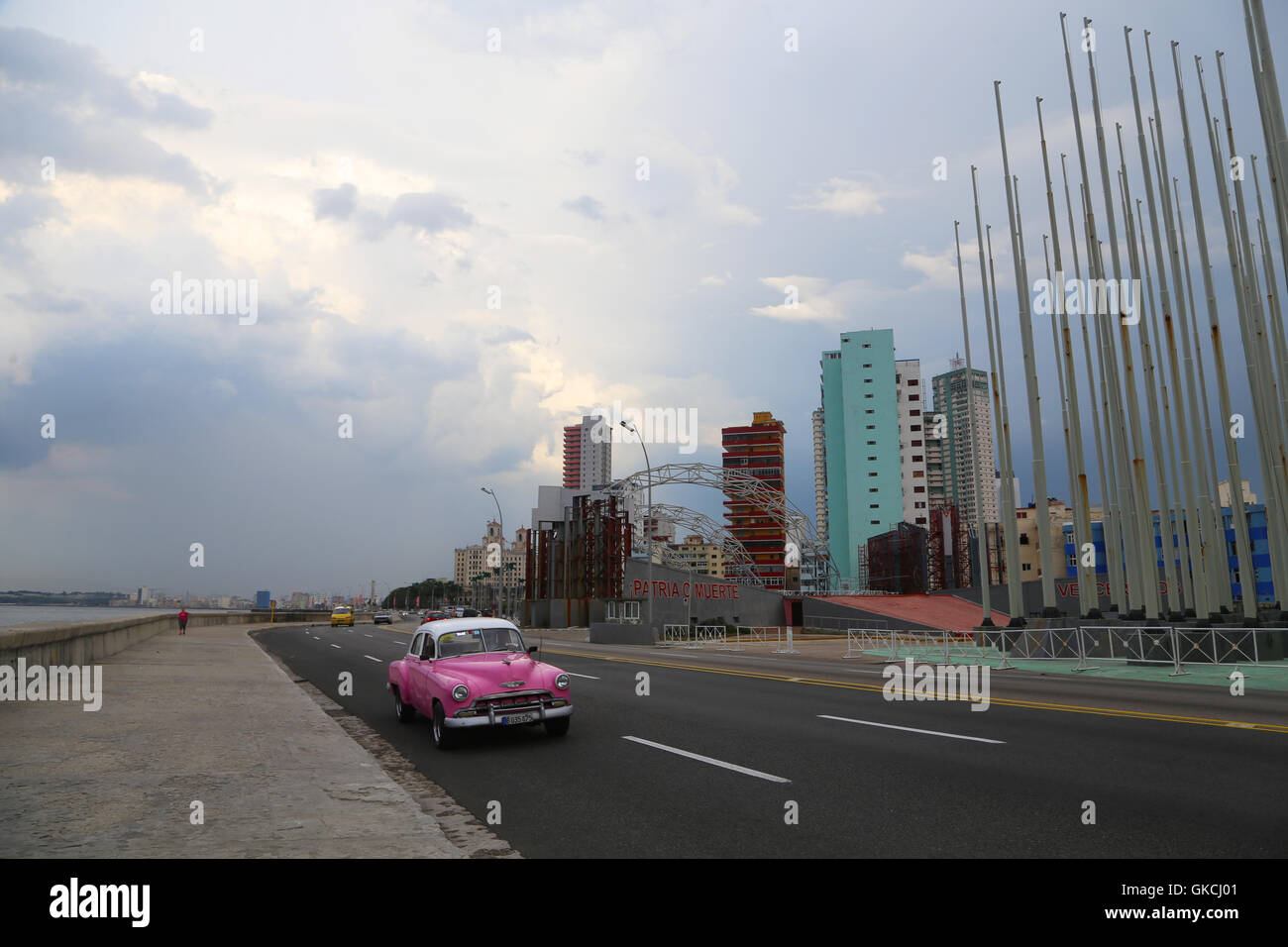 Cars drive along the Malecón at sunset, past the U.S. Interests Section building and Anti-Imperialist Plaza, - Stock Image