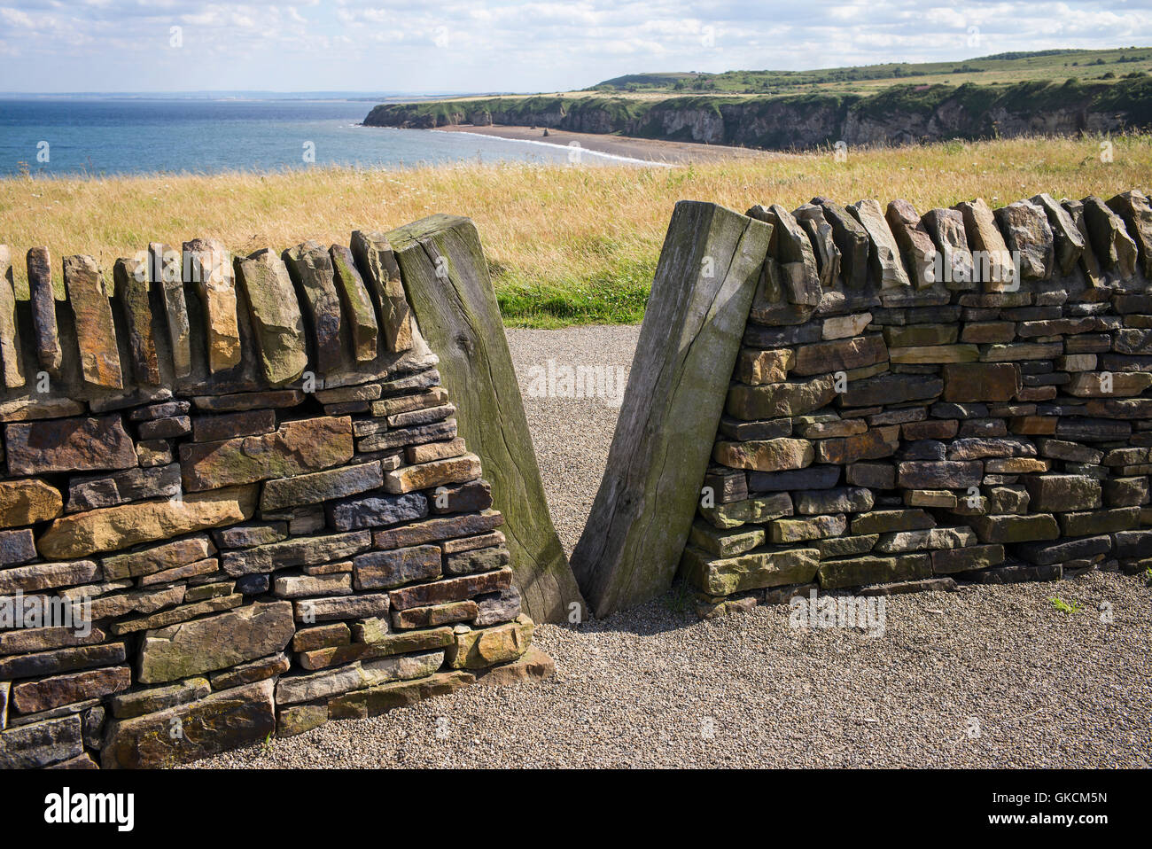 Wooden v shaped gap in a handcrafted stone wall at Nose's Point, Dawdon, Seaham, County Durham, UK - Stock Image