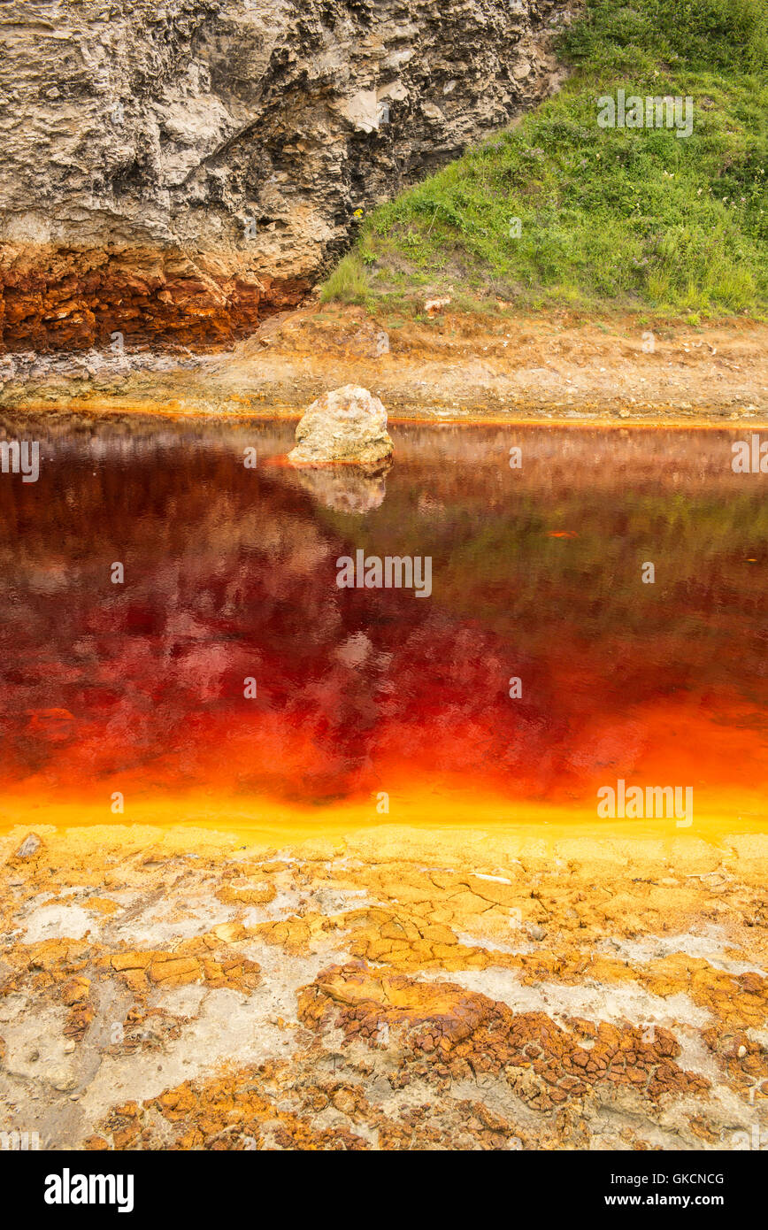 Water polluted from the residue of waste material from coal mining activity that was dumped on Blast Beach, County - Stock Image