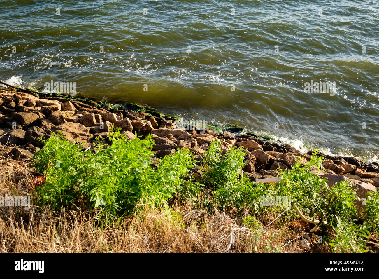 Rip-rap, or shot rock for erosion control lines the banks of Hefner lake in Oklahoma City, Oklahoma, USA. - Stock Image