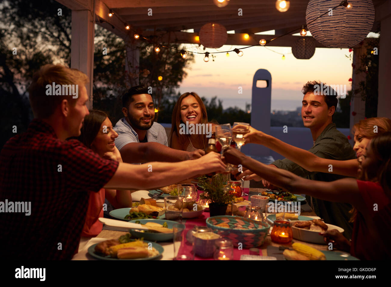 Friends Make A Toast At A Dinner Party On A Patio Close