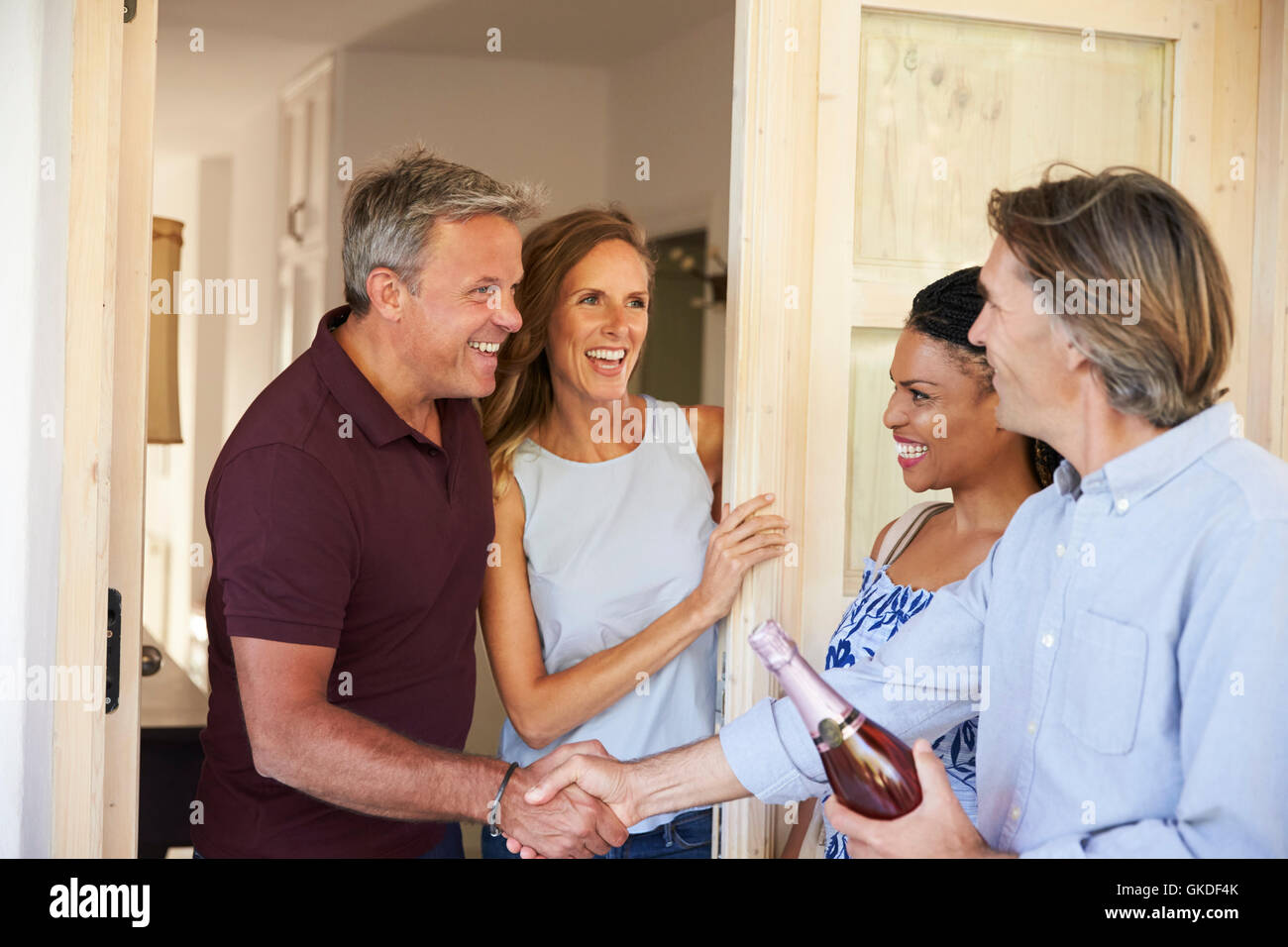 Couple greeting their guests at the door of their home - Stock Image