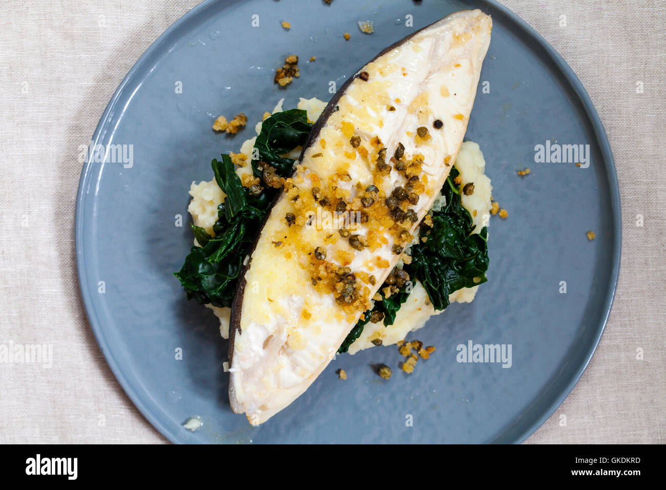 Halibut steak on potato mash with cavolo nero cabbage and capers and breadcrumbs butter - Stock Image
