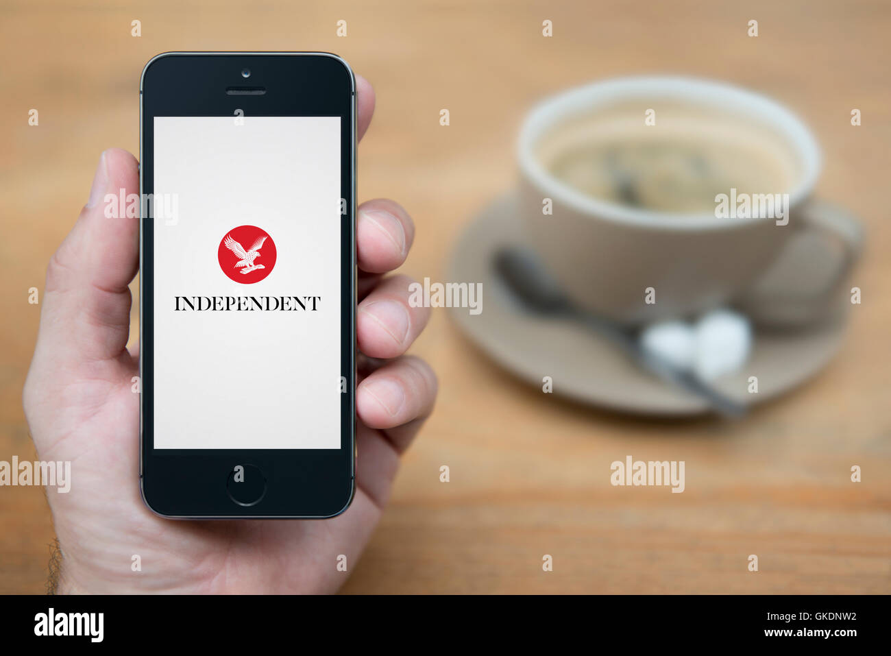 A man looks at his iPhone which displays the Independent logo, while sat with a cup of coffee (Editorial use only). - Stock Image