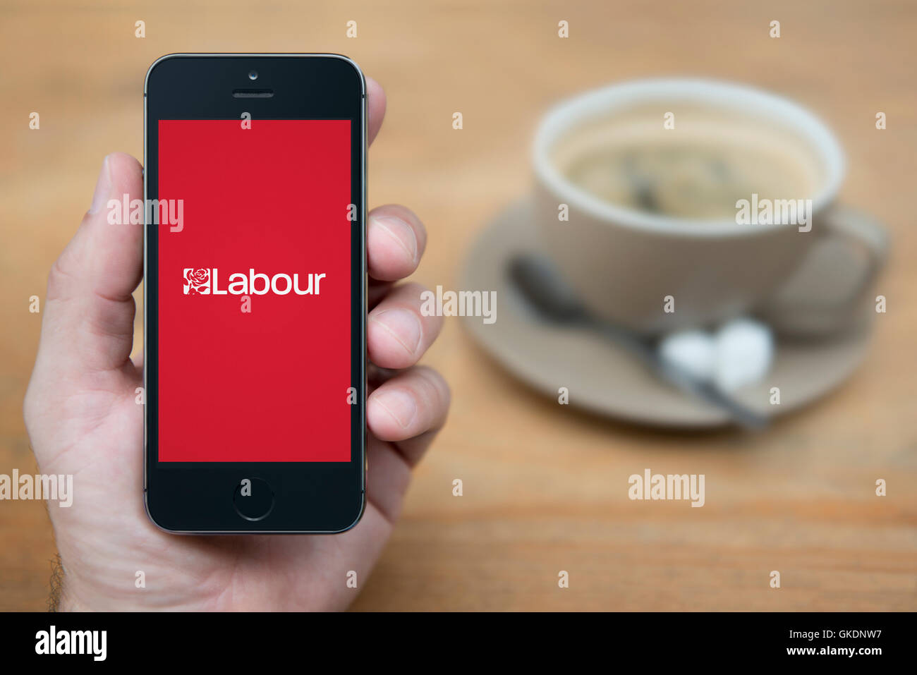 A man looks at his iPhone which displays the Labour Party logo, while sat with a cup of coffee (Editorial use only). - Stock Image