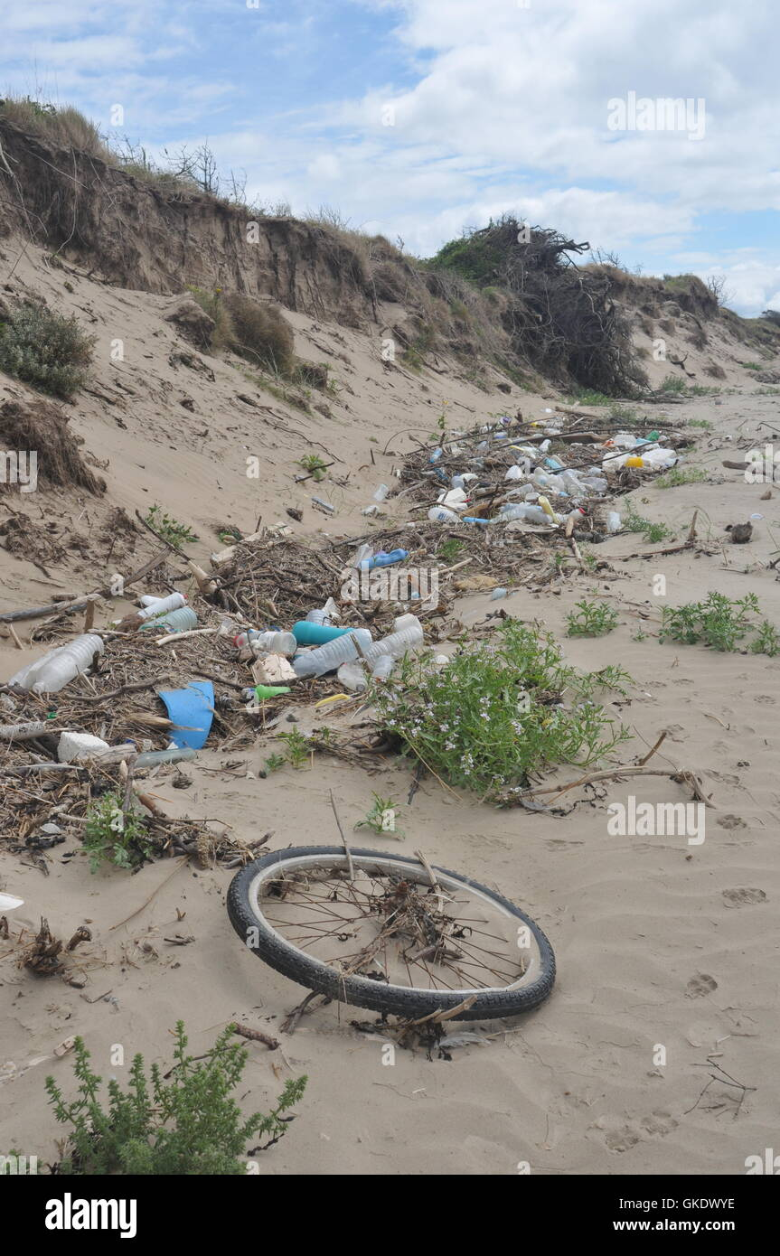 This is washed up rubbish on a sandy beach including plastic bottles a bicycle wheel, rope, food containers - Stock Image