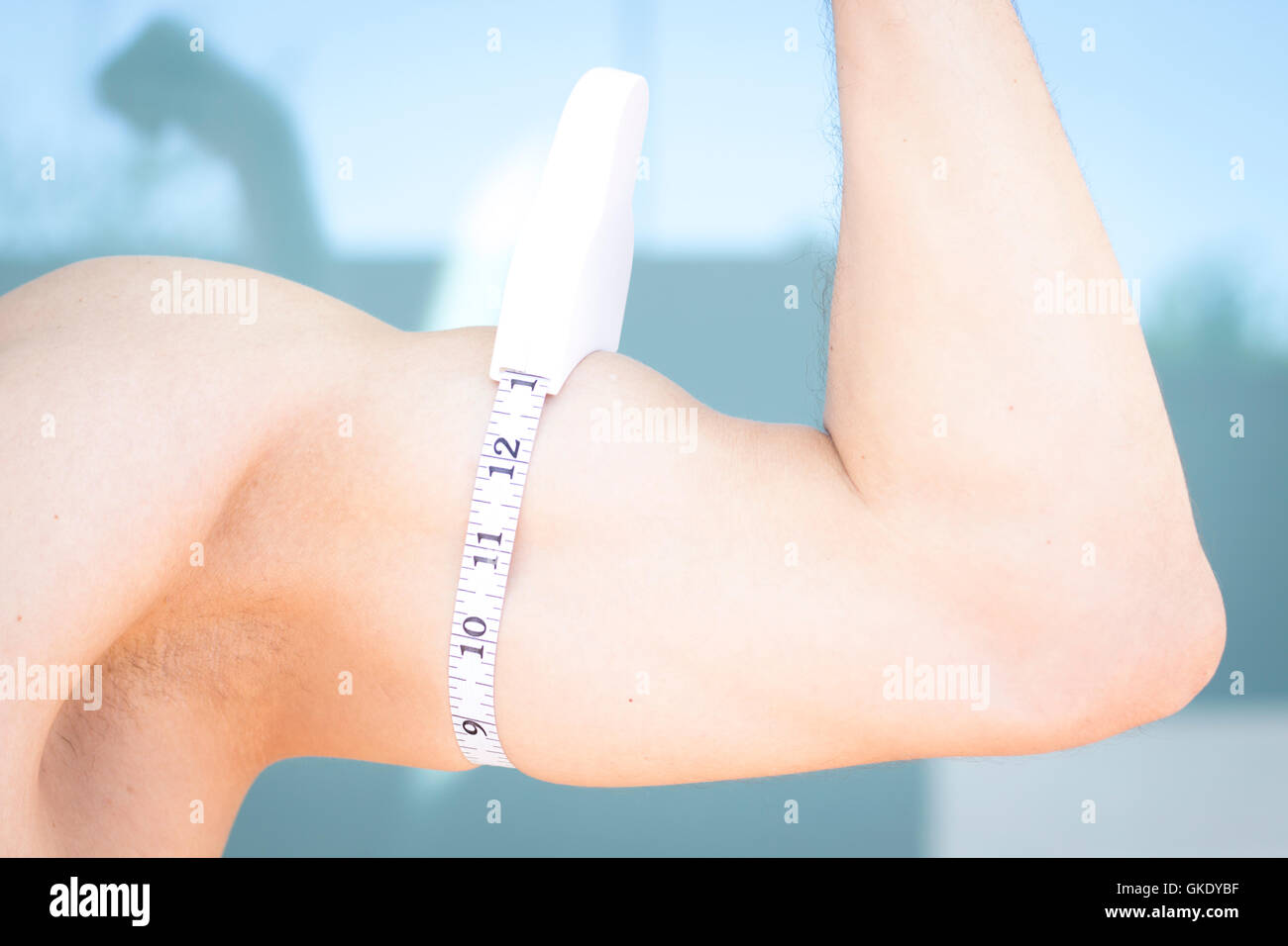 slim attractive young man using measuring tape to measure weight