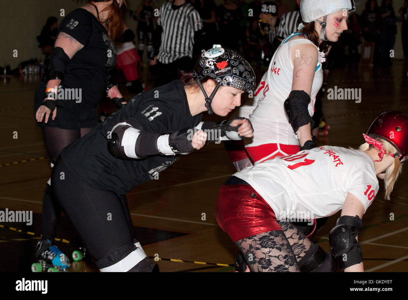 Woman roller derby skater in black avoids a booty block from an opponent - Stock Image