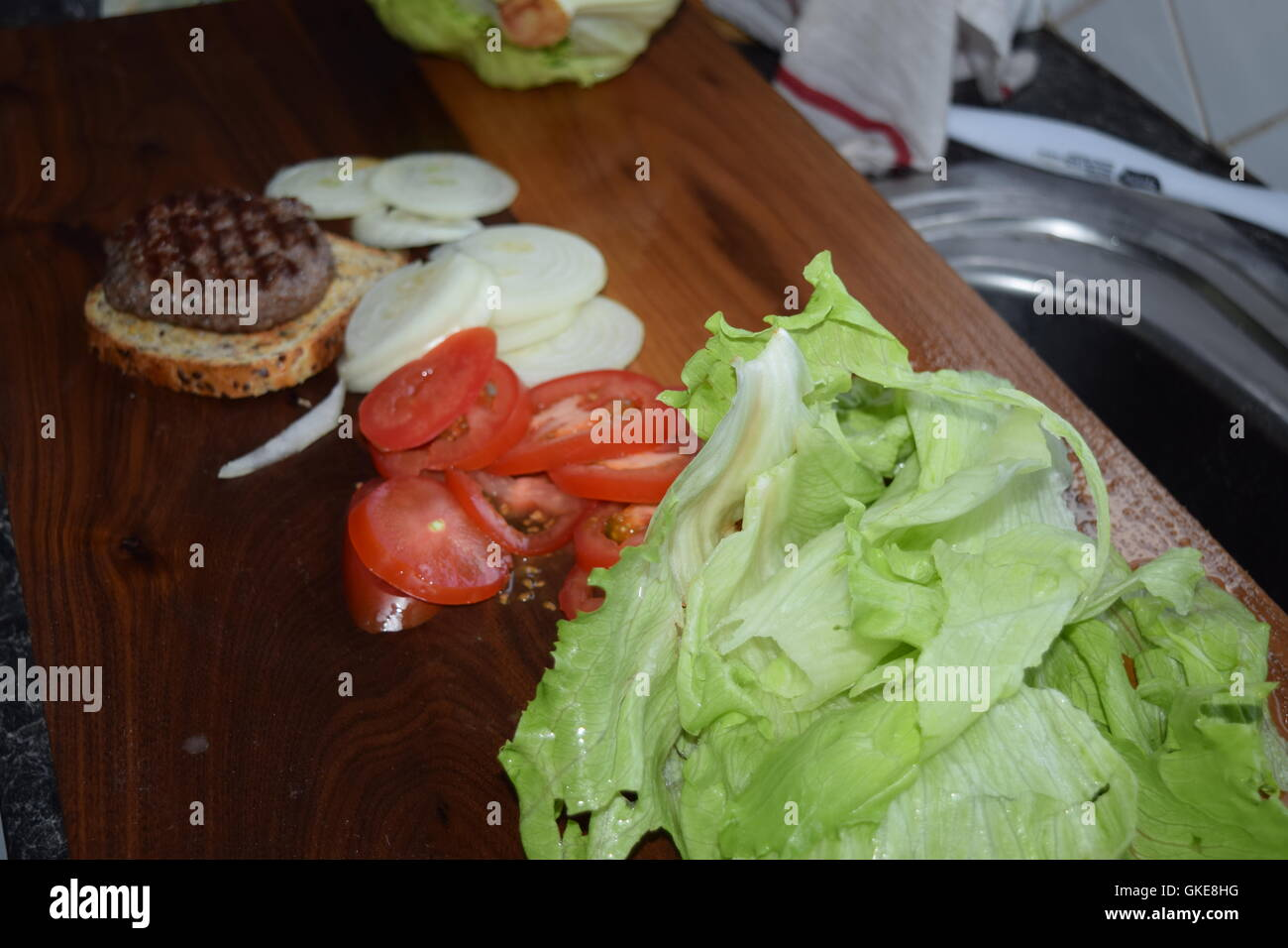 Vegetables with a Hamburger on Bread Stock Photo