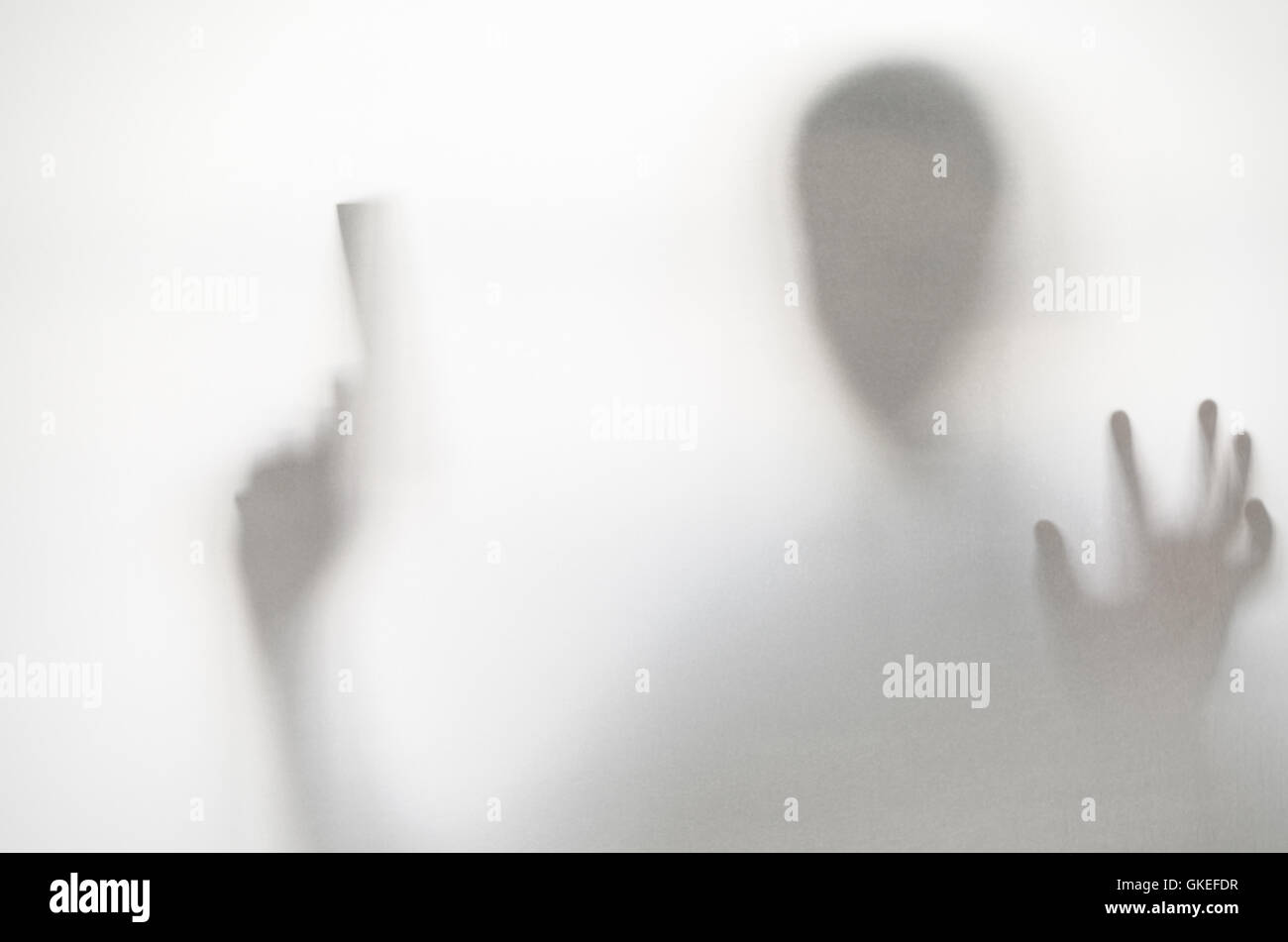 Spooky man behind curtain. Hands and blurry human figure abstraction. Stock Photo