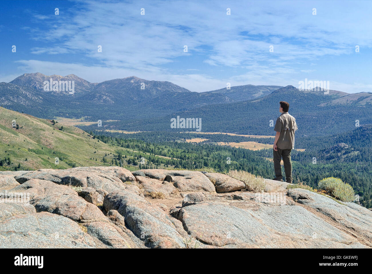 Young man looking at canyon from Frog Lake overview, near Carson Pass at Sierra Nevada, California - Stock Image