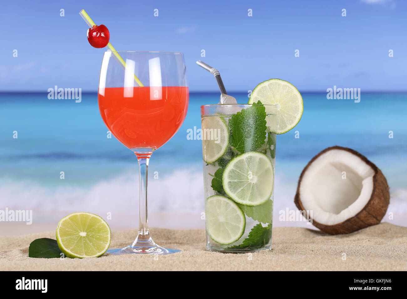 cocktails and drinks on the beach with sand and sea - Stock Image