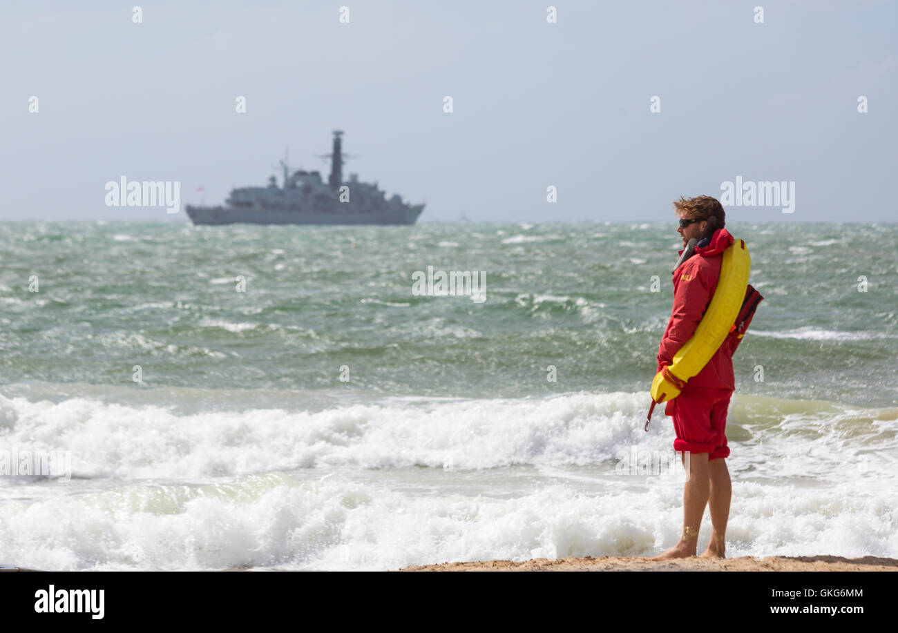 Bournemouth, UK. 20 August 2016. RNLI Lifeguard standing on seashore with wind and high tides causing disruption - Stock Image