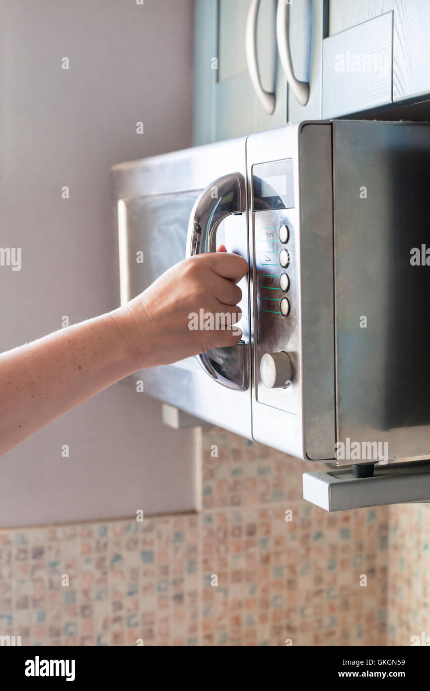 hand closes door of microwave oven for heating food - Stock Image