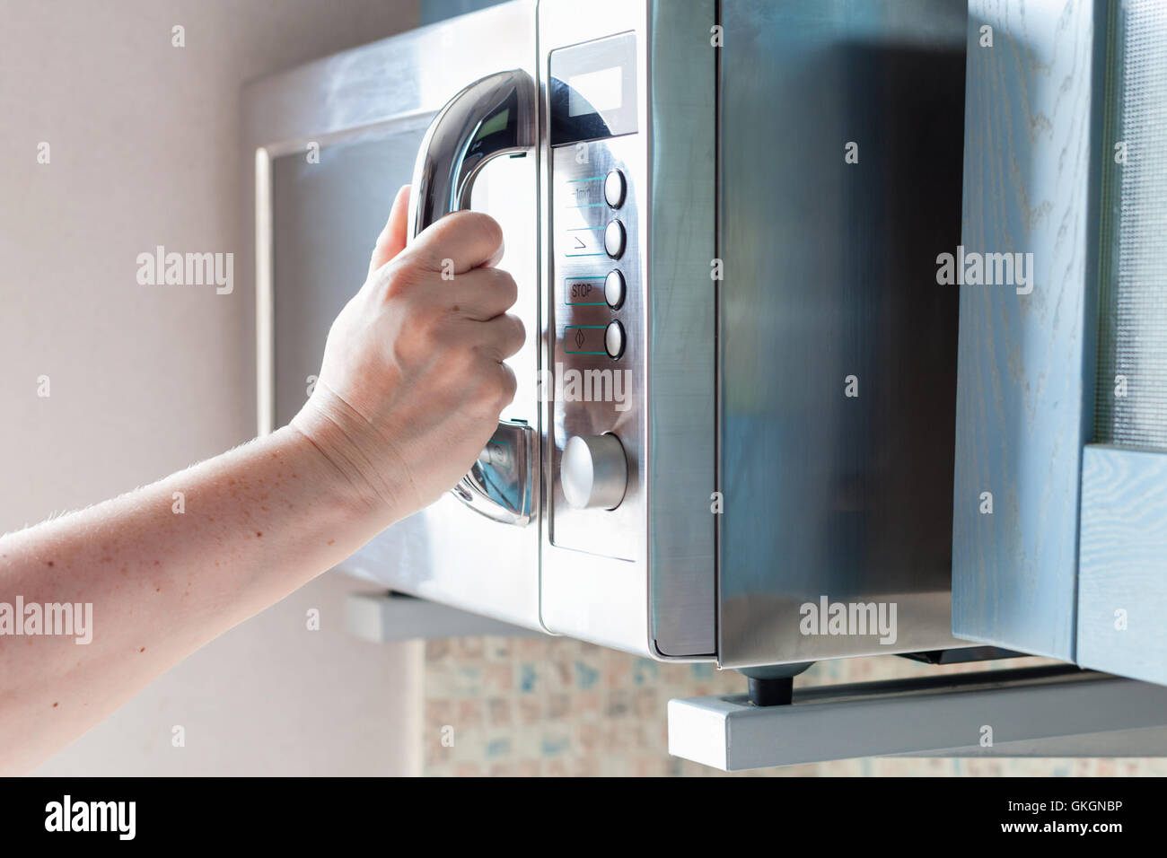 hand closes door of microwave oven for cooking food - Stock Image