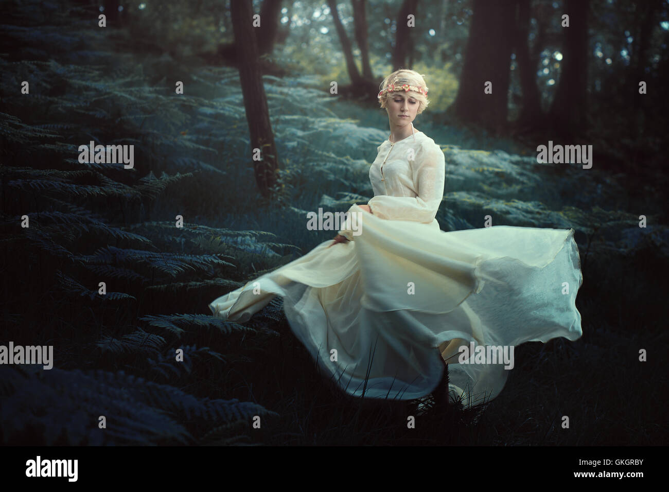 Ethereal woman dancing in dreamy forest. Fantasy and surreal - Stock Image