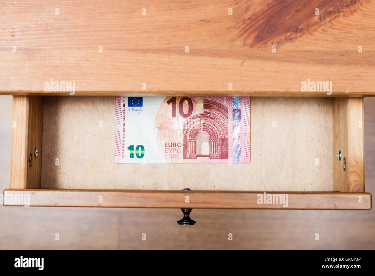 top view of one ten euro banknote in open drawer of nightstand - Stock Image