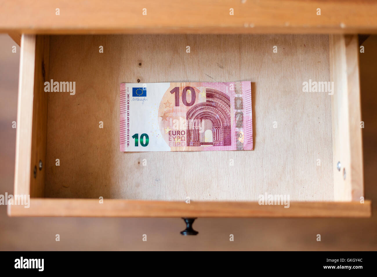 above view of ten euro banknote in open drawer of nightstand - Stock Image