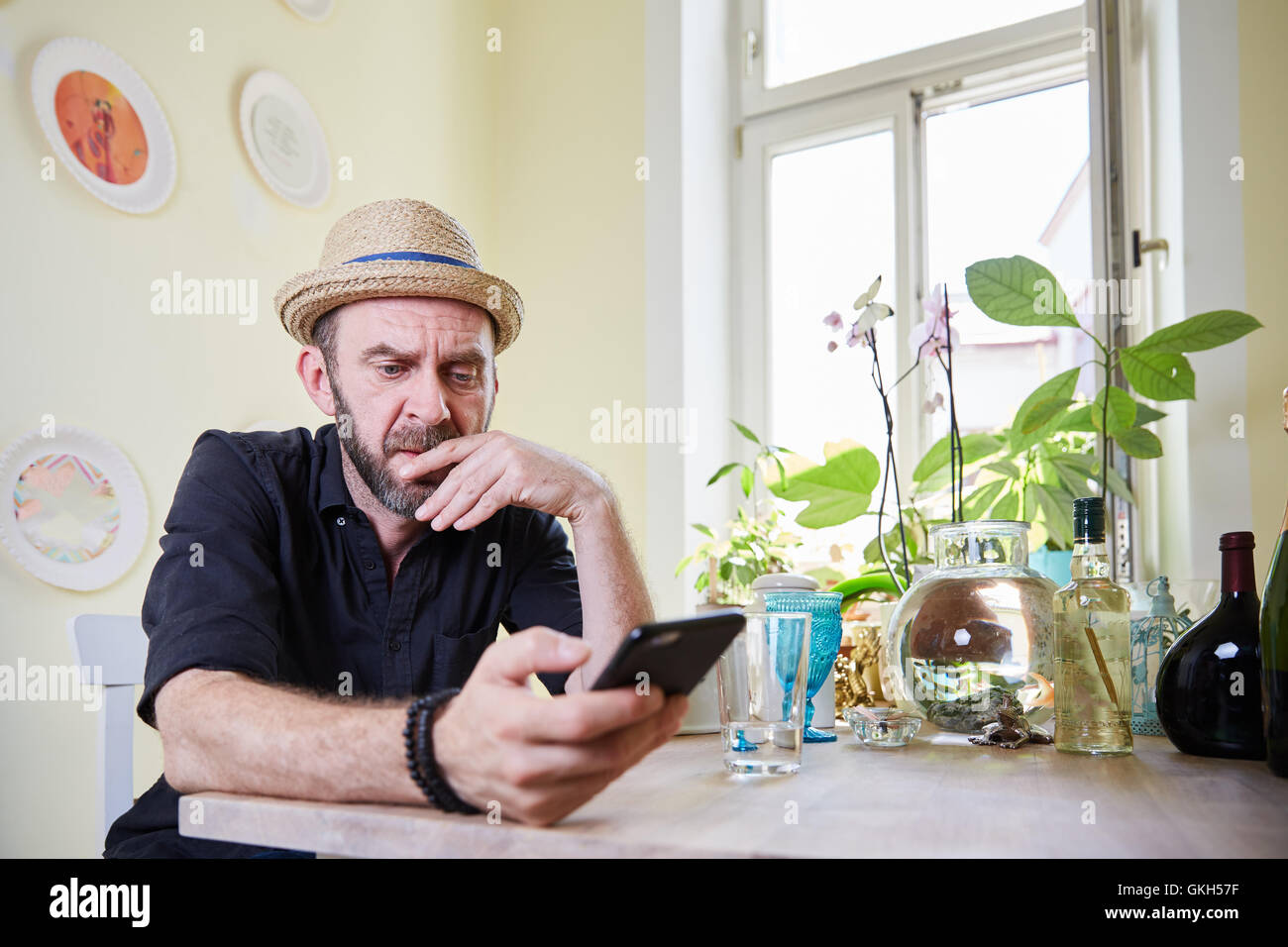 Man with hat and beard sitting and pondering in kitchen - Stock Image