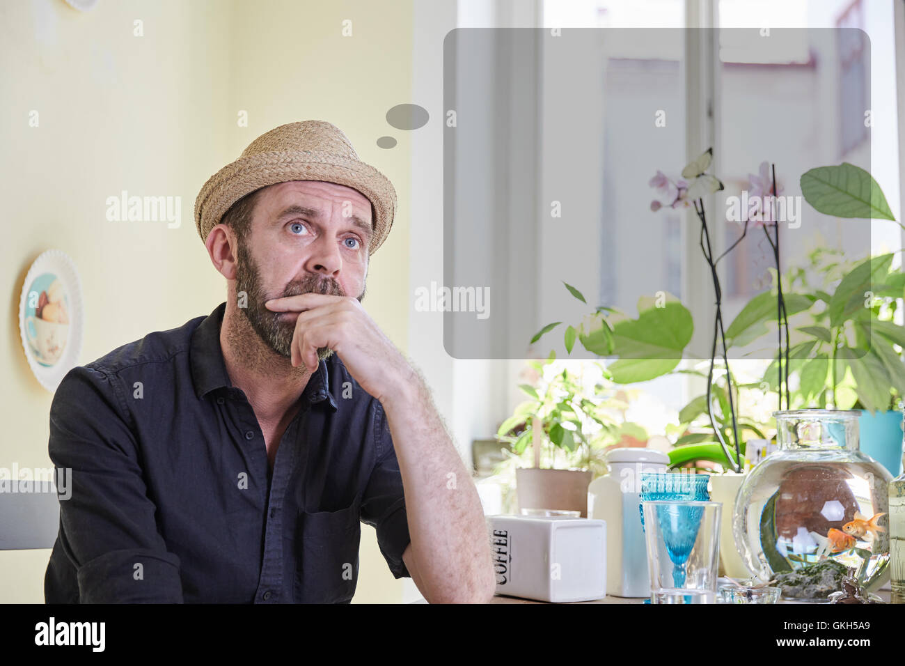 Man musing with a thought bubble over his head sitting in a kitchen indoors - Stock Image