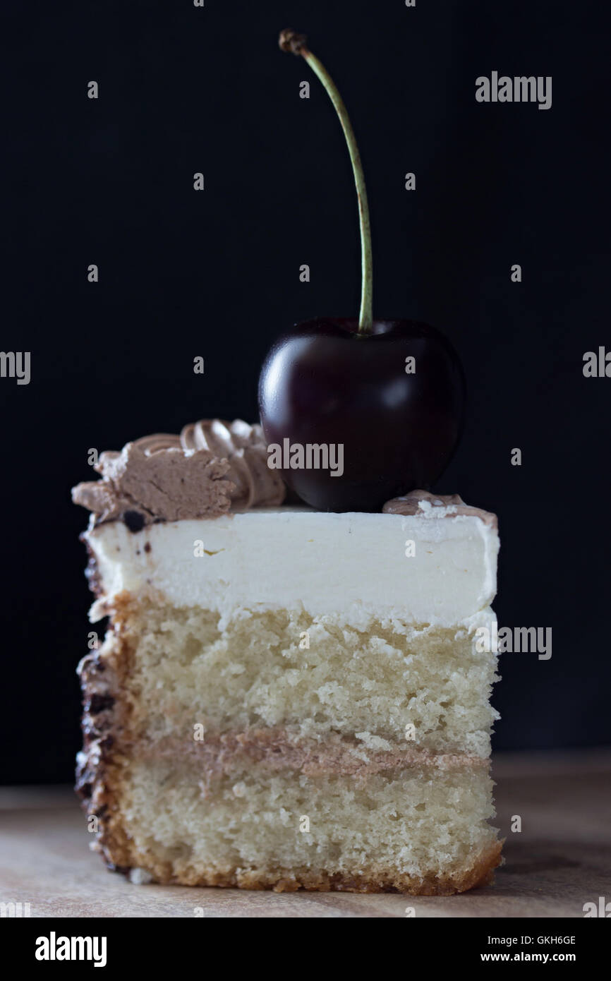 slice of cake with cherry on top, dark colours, toned - Stock Image