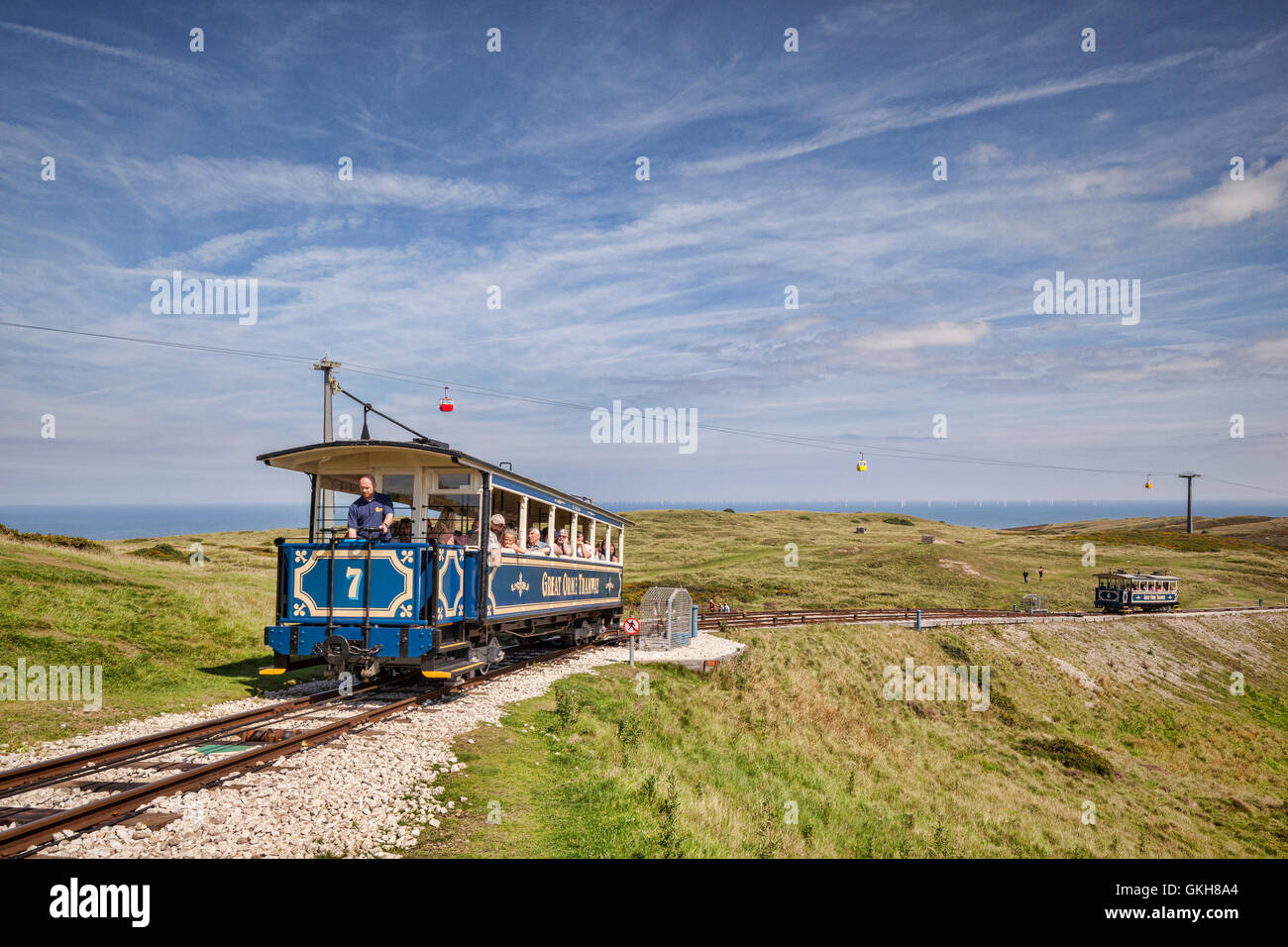 A passenger car of the Great Orme Tramway climbs from the upper passing loop as the descending car continues down, - Stock Image