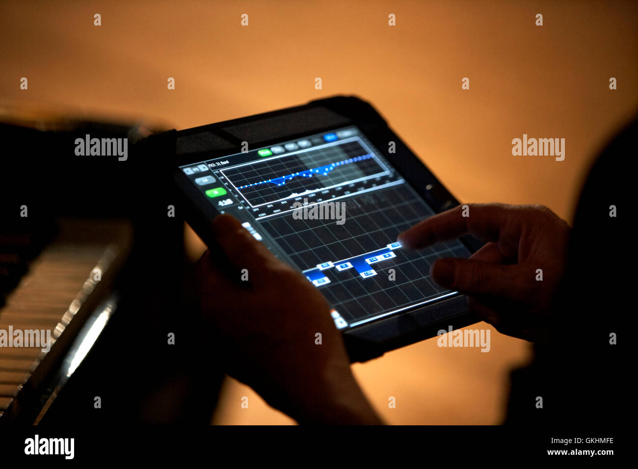 piano tuner tuning piano using tablet computer - Stock Image