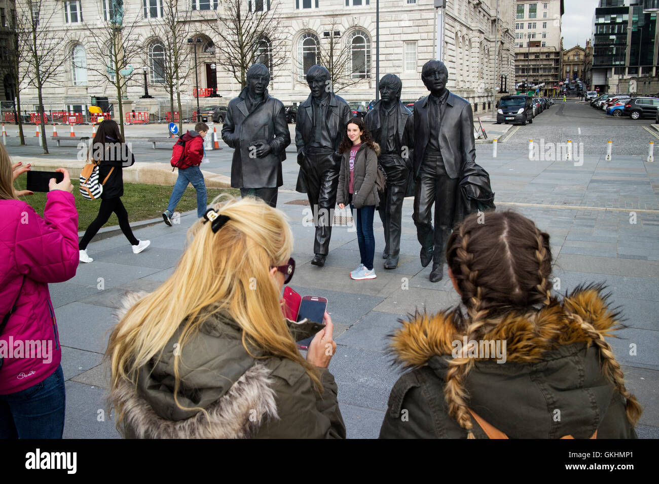 female tourists taking photos at The Beatles statue sculpture at Pier Head on Liverpools waterfront - Stock Image