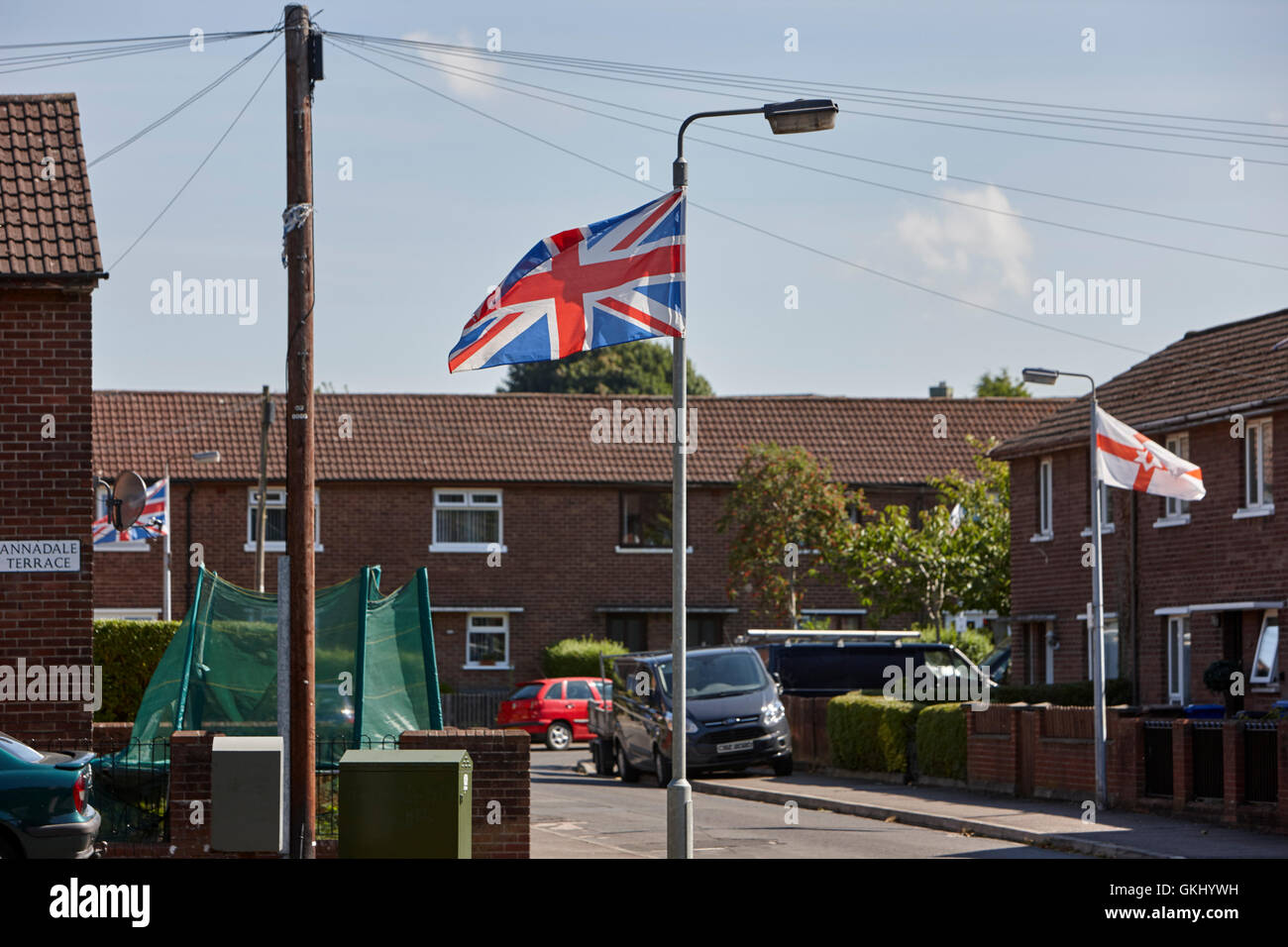 union and northern ireland flags hanging from lamposts in loyalist area of belfast - Stock Image