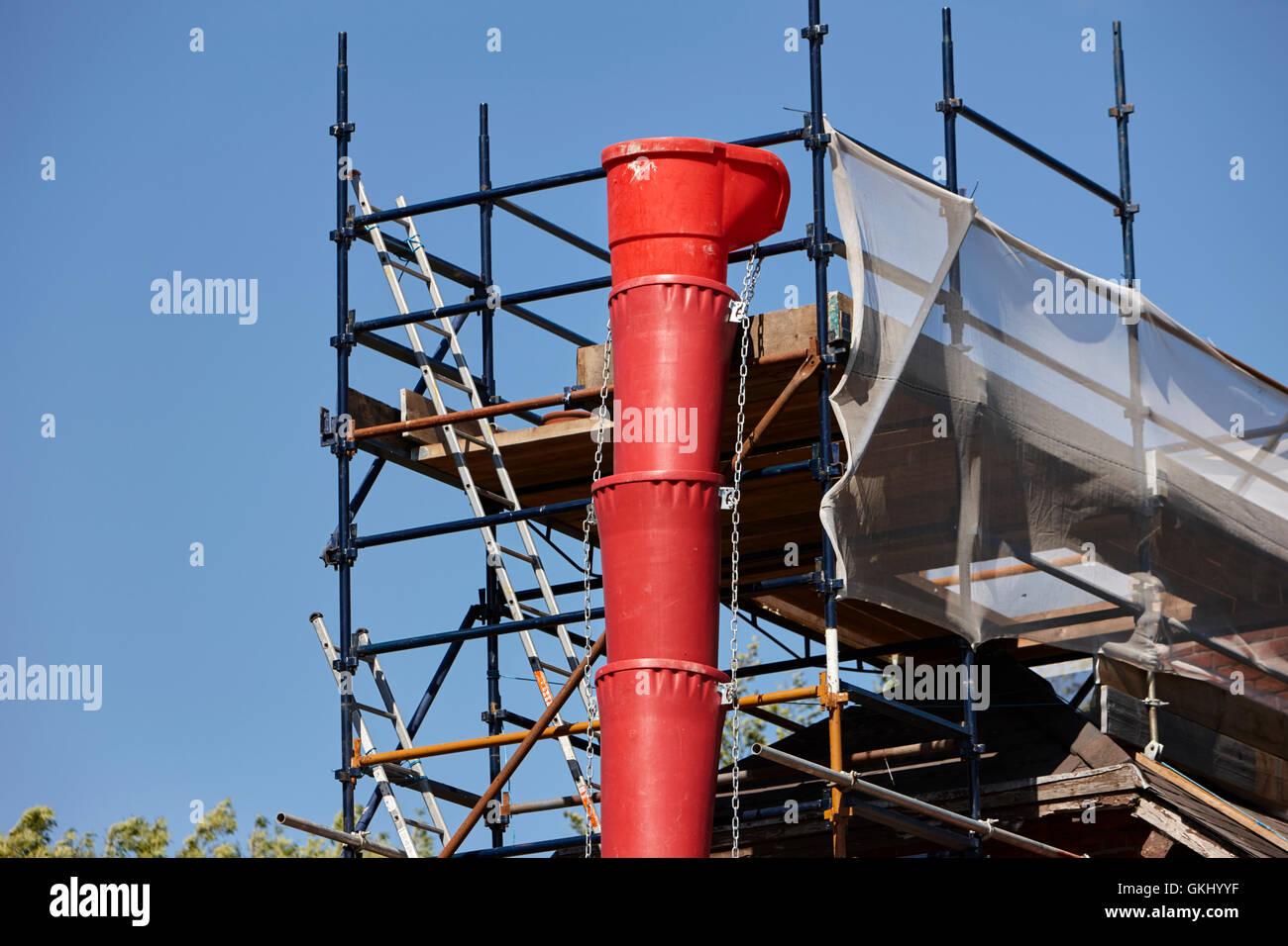 plastic rubbish chute attached to scaffolding on house extension in the uk - Stock Image