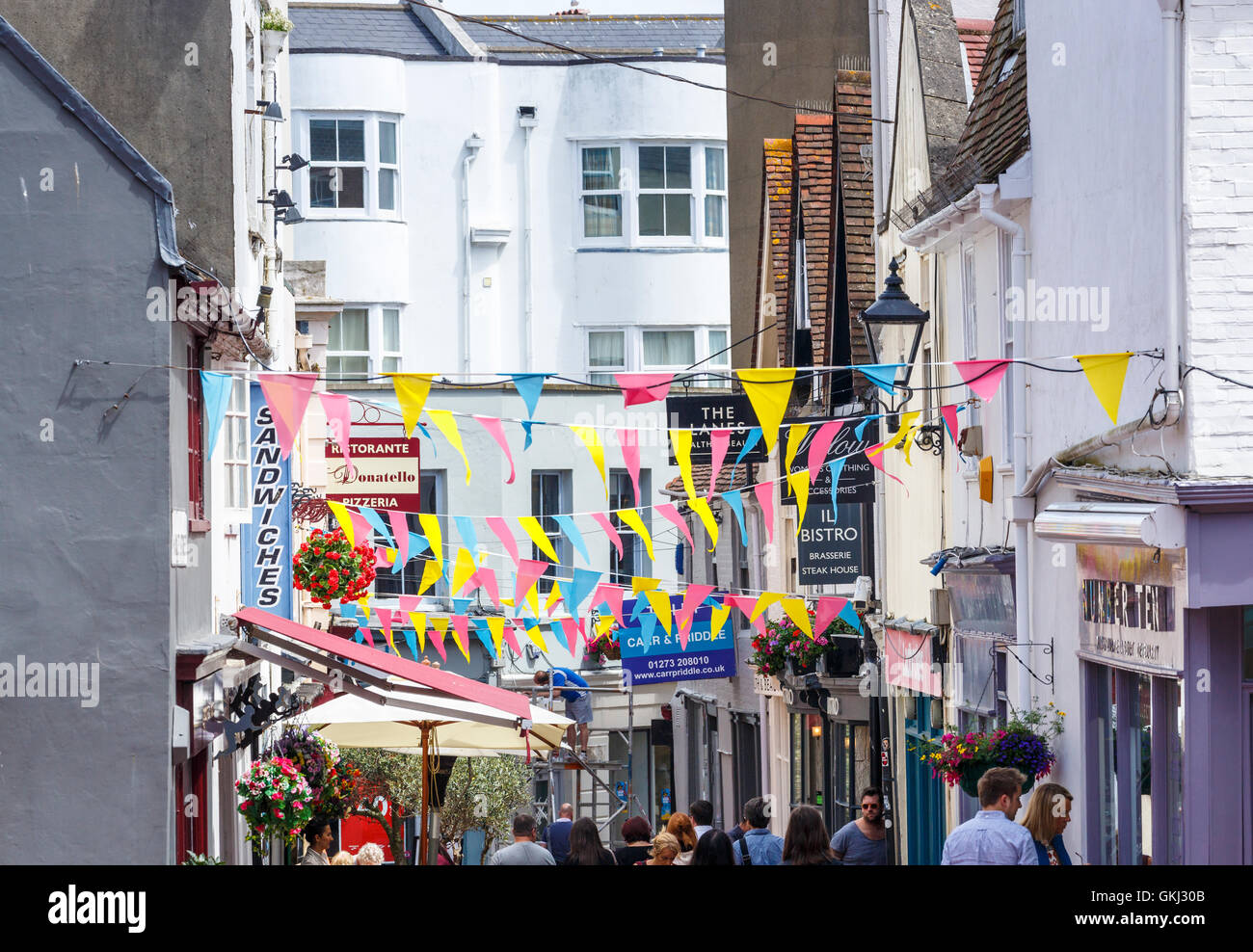 The Lanes, Brighton, East Sussex, UK with shop, restaurant and cafe signs and colourful bunting - Stock Image