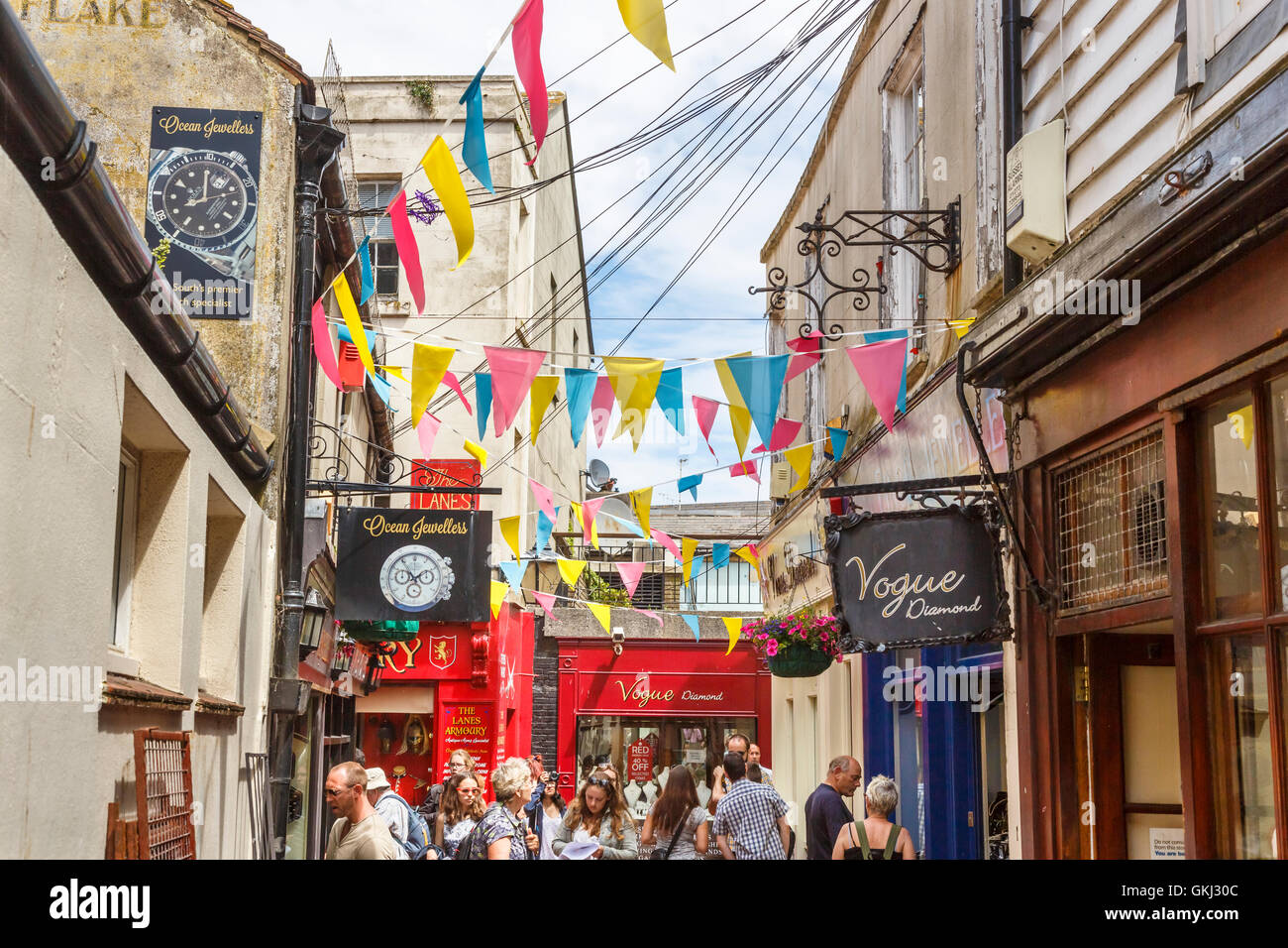 Shop signs and colourful bunting in The Lanes, Brighton, East Sussex, UK on a sunny summer day - Stock Image